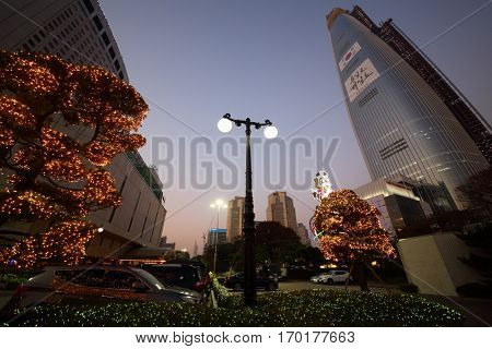 SEOUL - NOV 3, 2015: Illuminated trees, big raccoon and highrise buildings in Lotte World with car parking. Amusement park Lotte World each year receives more than 8 million visitors