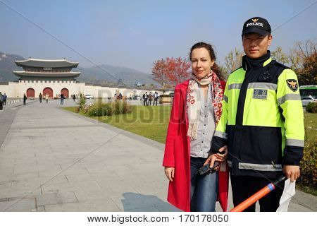 SEOUL - NOV 2, 2015: Woman (with model release) poses with policemen near gate to palace Gyeongbokgung with pagoda. Gate to royal palace of Gyeongbokgung is important symbol of Korea