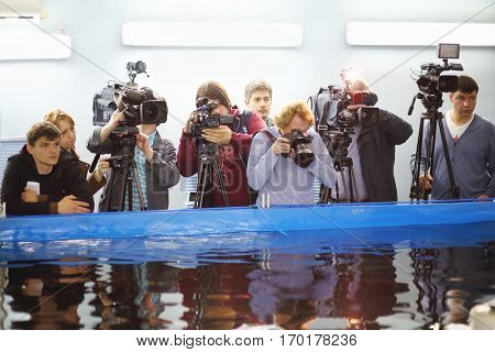 MOSCOW, RUSSIA - APR 28, 2016: Videographers near pool during excursion at Fish-packing Factory (Marine Castle)