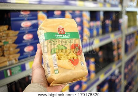 MOSCOW, RUSSIA - APR 27, 2016: Male hand holds package of pasta in METRO market. Fine life is own brand METRO