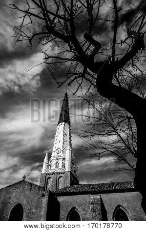 Dramatic black and white view of Saint-Etienne church spire Village of Ars en Re Ile de Re France
