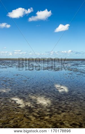 Maritime landscape with reflection of clouds in low tide water, Waddenzee, Friesland The Netherlands