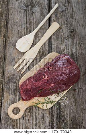 Beef Steak With Fresh Herbs On Wooden Board.