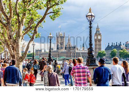 LONDON - JUNE 11, 2011: Crowd of people walking on The Queen's Walk promenade part of Jubilee Walkway route