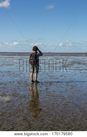 Maritime landscape at low tide water with a man mud walking and looking at the vieuw Waddenzee Friesland The Netherlands