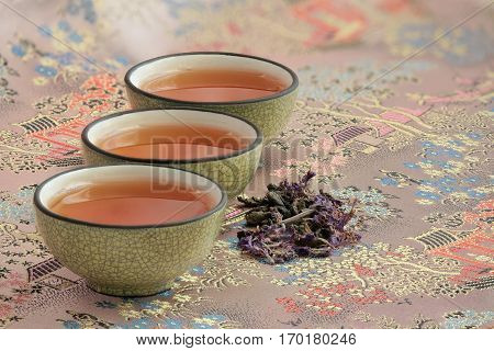 three cups filled with tea on a beautiful tablecloth and a pinch of fragrant flower tea