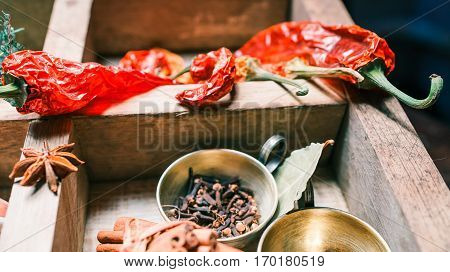 Dried chili and allspice amid other spices and herbs on cooking table. Close up view. Selective focus