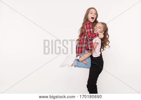 Happy two little girls sisters screaming, rejoicing and embracing each other isolated on white background