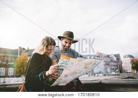Young Tourist Couple Looking At A Navigational Map.
