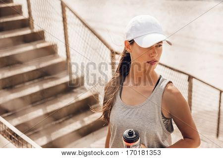 Shot of beautiful young woman in hat standing at the beach holding water bottle and looking away. Fitness female taking a break after workout.