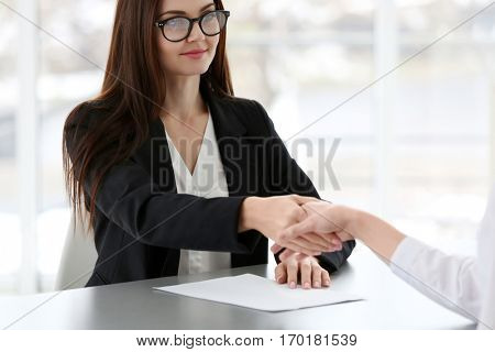 Job interview concept. Human resources manager shaking woman's hand, closeup
