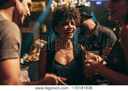 Shot of young african woman enjoying at nightclub with friends. Group of people having good time at pub.
