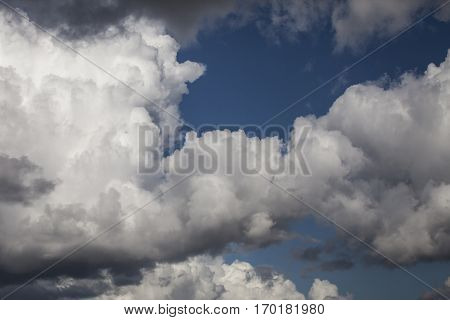 White fluffy storm clouds in blue sky