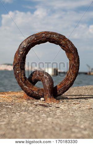 old rusty dock mooring ring on concrete quay
