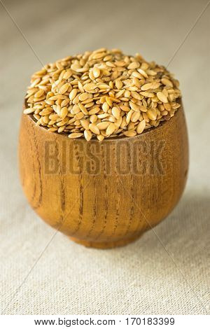 Flax seeds in a wood bowl on linen cloth, close up