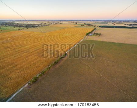 Aerial View Of Harvested Agricultural Field And Pastures At Sunset In Rural Australia.