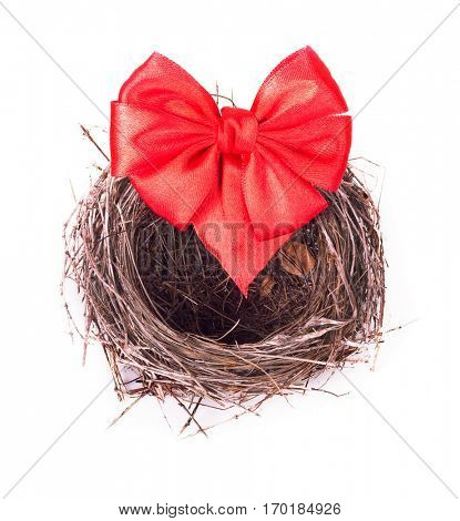 Empty nest with a red bow isolated on white background