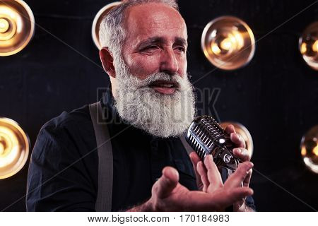 Extreme close-up of man singing into microphone. Senior man in official dark shirt and suspenders. Isolated over spotlights