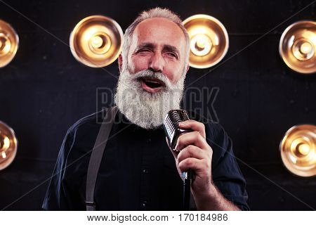 Live performance of exhilarated handsome senior male singer in shirt and suspenders while holding silver vintage microphone. Singing man with retro microphone. Vintage style song