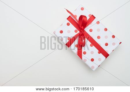 Top view of big dotted gift box with red ribbon and bow tie. Isolated over flat layout with copy space