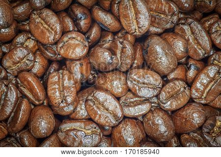 Coffee beans closeup. Roasted brown coffee beans texture or coffee beans background for design. Dark edged.