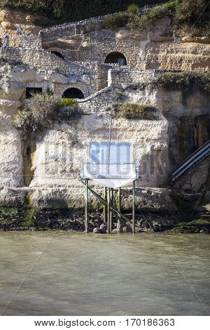 traditional french fisherman's wooden hut at the bottom of the limestone cliff in the estuary of Gironde Meschers-sur-Gironde