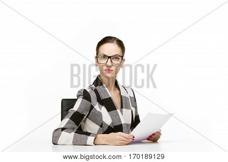 Self reliant business woman sitting at workplace with papers or documents, white background