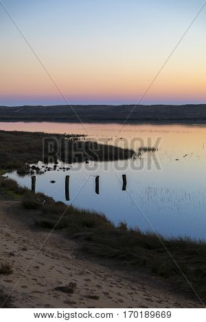 sunset with reflection in still water over nature reserve Casse de la Belle Henriette, l'Aiguillon sur Mer,  Vendee, France