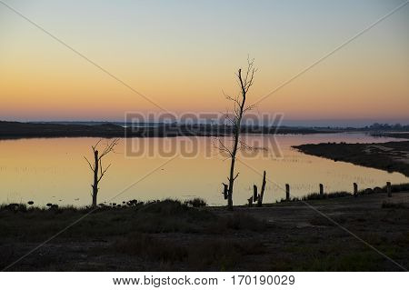 sunset with reflection in still water over nature reserve Casse de la Belle Henriette Vendee France