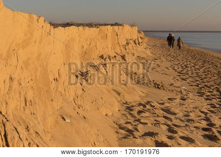 people walking on the beach by romantic winter sunset, Casse de la Belle Henriette, located between l'Aiguillon sur Mer and la Tranche sur Mer, Vendee, France