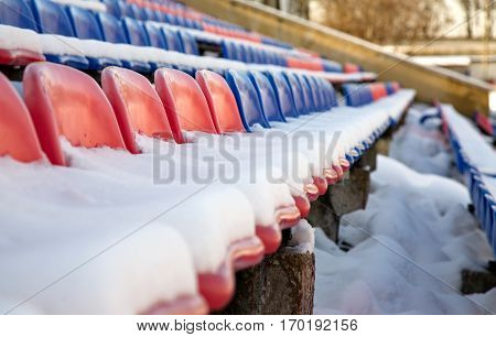 Partially snow covered red and blue seats in the stadium.