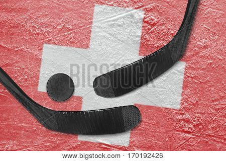 Hockey puck hockey sticks and the image of the Swiss flag on the ice. Concept