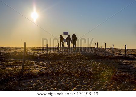 Silhouette of people walking on the beach by romantic winter sunset at nature reserve Casse de la Belle Henriette, located between La Tranche Sur Mer and l'Aiguillon sur Mer , Vendee, France