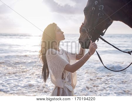 Happy fashionable young woman posing with a horse on the beach