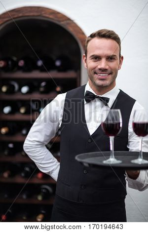 Waiter with tray of red wine in a commercial kitchen