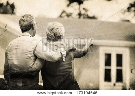 Grey background against senior couple looking at house while standing ih yard