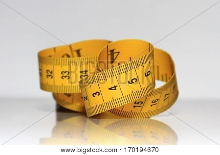yellow measuring tape is lying on a shiny