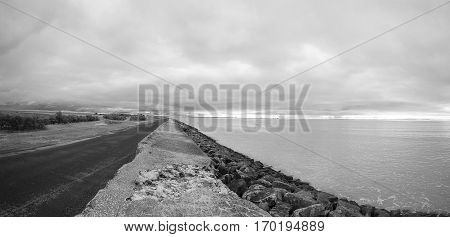 Black and white Panoramic view of the coastline and dike proctecting the village of l'Aiguillon sur Mer Vendee France