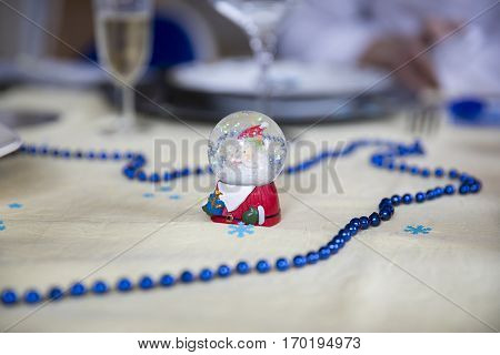 Christmas table decorated with little Santa figurine in glitter snowball