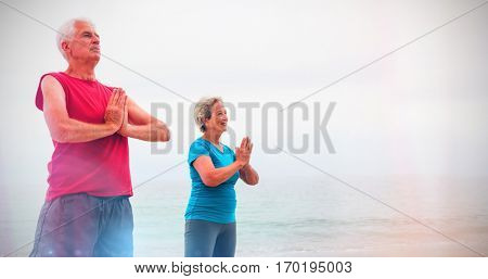 Senior couple in lotus position on the beach on a sunny day