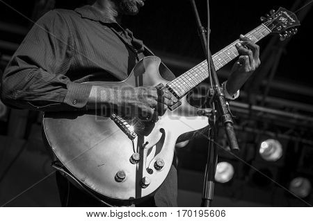 close up on a man playing electric guitar