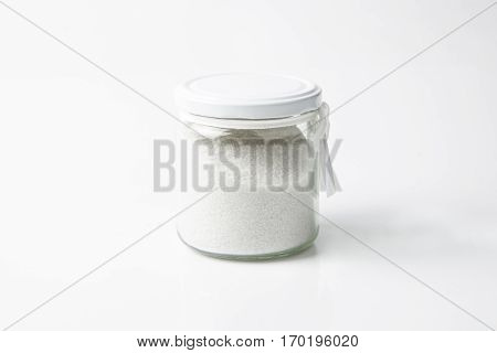 glass jar with salt or bath salt isolated in white background