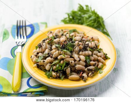 salad with  beans black olives and arugula, selective focus