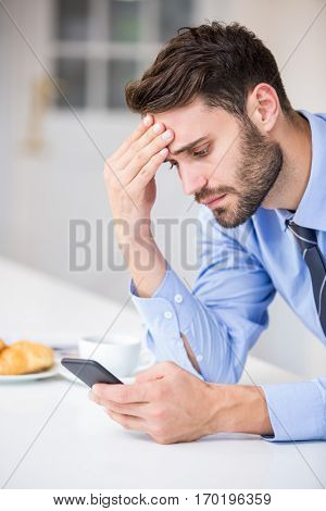 Close-up of tensed businessman using mobile phone by table at home