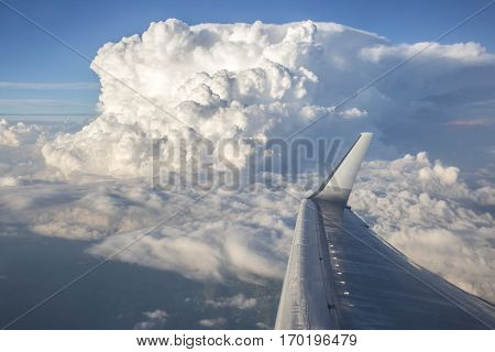 White fluffy storm clouds with an airplane wing