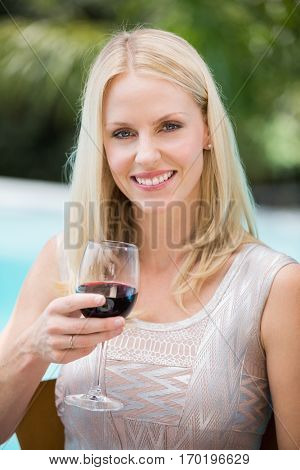 Portrait of smiling young woman holding red wine glass at poolside