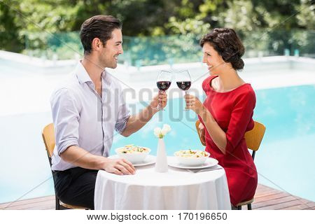 Smiling couple toasting red wine while sitting at poolside