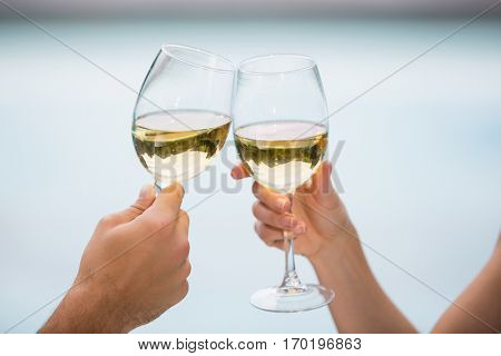 Cropped hands of couple toasting white wine at poolside