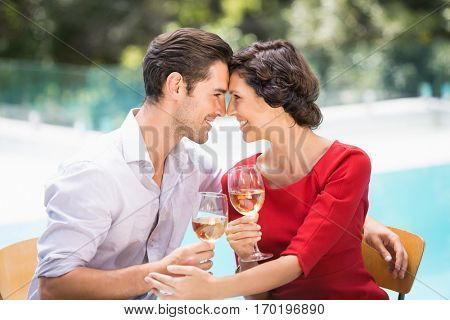 Romantic couple holding white wine while sitting at poolside