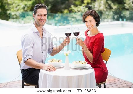 Portrait of smiling couple toasting red wine while sitting at poolside